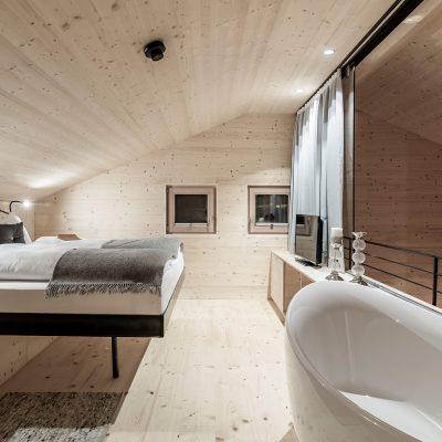 Ferienimmobilie zum Verkauf: Suite mit Badewanne vor Panoramafenster